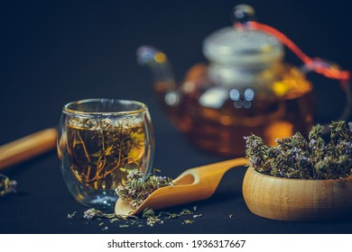 Thyme tea's cup, teapot,  thyme flower on black background. Herbal tea in  wooden spoon and bowl.