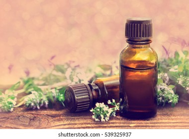 Thyme (thymus) essential oil on flowers and plants background, toned