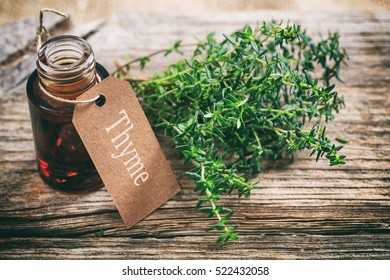 Thyme twig and thyme oil on wooden background
