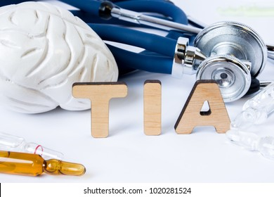 TIA Acronym or abbreviation to medical concept or diagnosis of transient ischemic attack or small brain stroke. Word TIA stands among models of the brain, stethoscope and medicines in ampules or vials