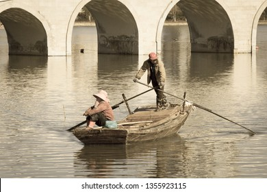 Tianjin / China - 03 24 2019 : An old couple riding a sampan in a canal under a bridge