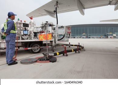 Tianjin, China, August 2019, fuel truck and fuel truck driver refueling an airplane on apron of Tianjin Binhai International Airport (TSN, ZBTJ)
