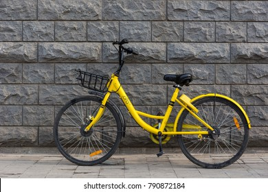 Tianjin, China - December 23, 2017 : Side View of yellow OFO bikes with Gray wall background. OFO is popular bike sharing platform in china.