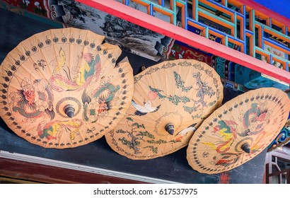 Tianjin, China - Nov 1, 2016: Closeup of three decoratively painted umbrellas under eaves of a traditional building along the famous Tianjin Ancient Cultural Street (Guwenhua Jie).
