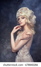 Tiara crown on head blonde girl. Woman in fairy dress, mysterious magical fairy. Ethnic blond woman on gray background