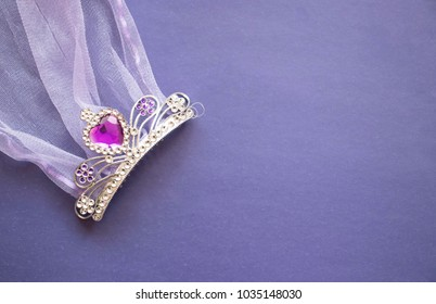 tiara on a purple background. Wedding and girl's party concept. children's crown with ruby heart, copy space