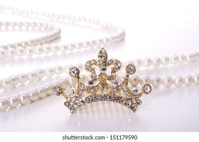 tiara and pearl necklace on white