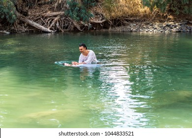 Tiberiades, Jordan River, Israel, 03/09/2016 Family being baptized in The Baptismal Site on The Jordan River.