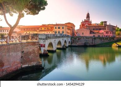 Tiberius bridge in Rimini historic centre, Italy. Scenic ancient stone bridge in morning sunrise. Beautiful famous landmark of Rimini