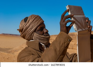 Tibesti, Chad - 31/12/2012. Young local man from Chad is making a photo by using tablet. In the backgroung dunes of Sahara.