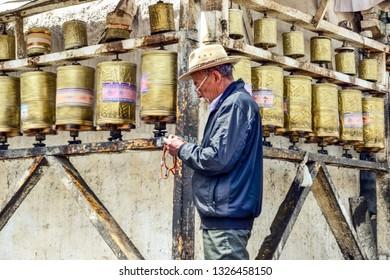 Tibet / China - April 27, 2012: Tibetan man spinning prayer wheels in the city of Lhasa