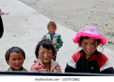 Tibet, China - June 14th, 2017: Four little Tibetan girls with smeared faces looked at the viewer in the face. The photo was taken in a remote village in Dingri County near Everest Base Camp.