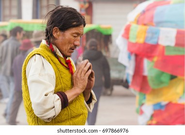 Tibet, China - May 05, 2012: Tibetan buddhism. Local Man stay against buddhist Jokhang temple and monastery and pray to increase his karma and to improve his life, Lhasa, Tibet, China