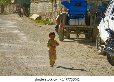 TIBET PLATEAU, CHINA, OCTOBER 2018: CLOSE UP: Adorable little Tibetan girl walks down the dusty gravel road on a sunny autumn day. Cute Asian child explores the poor rural town in the Himalayas.