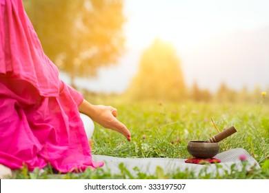 Tibetan bell beside yoga position in a meadow