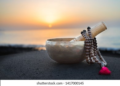 Tibetan bowl with mala beads on nature seaside background for meditation and mindfulness