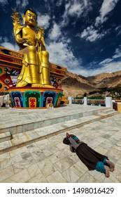 Tibetan Buddhist woman worshiping and praying Buddha Maitreya statue in Likir gompa (monastery), Ladakh, India