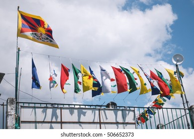 Tibetan flag and colourful prayer flags in the wind, India