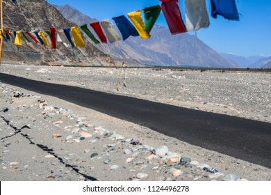 Tibetan flags flying along the road passing through the cold desert of Leh Ladakh region in India.
