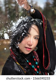 Tibetan girl playing with snow in the forest