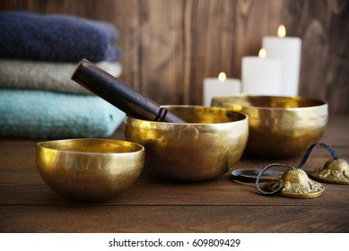 Tibetan handcrafted singing bowls with towels and candles on wooden background