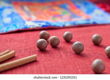 Tibetan herbal mix balls, incense sticks and buddhist thangka