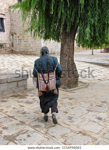 Tibetan man with braids, a striped back pack and traditional clothes walking near the Sera monastery, Lhasa, Tibet, China