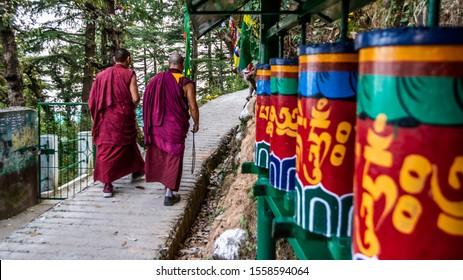 Tibetan Monks walking among praying wheels, Dharamsala, India