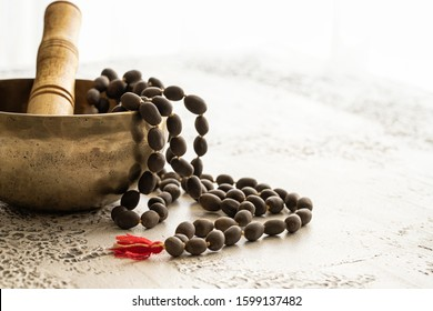 Tibetan music bowl  with mala beads on white concrete background with copy space. Essential accessory for mindfulness or meditation.