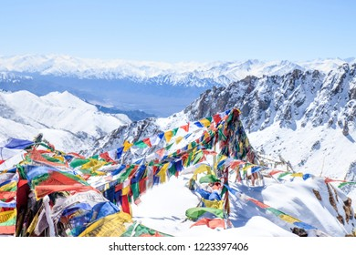 Tibetan prayer flags blowing in the wind on the top of snow mountain
