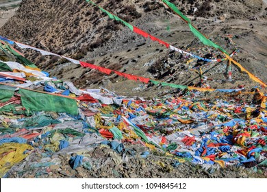 Tibetan prayer flags, colorful rectangular clothes, use to bless the surrounding countryside, blowing in the wind in Himalayas, herd of yaks in the background.