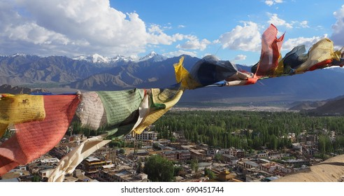 Tibetan prayer flags waving over Leh, India with Himalayas background