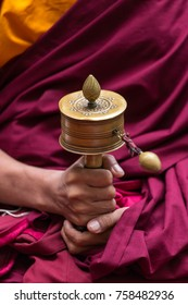 Tibetan prayer wheel in monks hands close-up