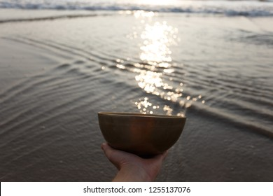Tibetan singing bowl by the sea, in which the sun's rays shimmer. On the background are gentle waves and play of sunlight. Hand holds a bowl. Sound therapy. Healing. The music of the soul.