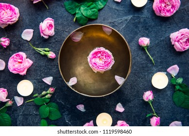 Tibetan singing bowl with floating rose inside. Burning candles, tea rose flowers and petals on the black stone background. Meditation and Relax. Exotic massage, spa procedure. Selective focus