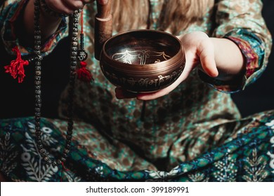 Tibetan singing bowl in the hands of a girl in national costume