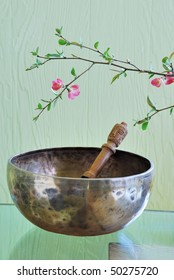 Tibetan singing bowl with mallet and flowering tree branch