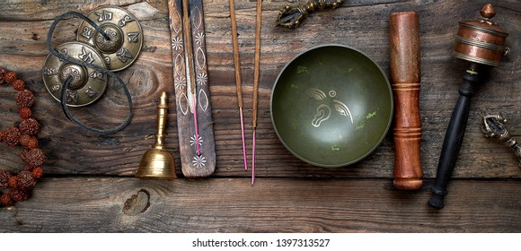 Tibetan singing bowl and other religious ritual instruments for meditation on a brown wooden background, top view
