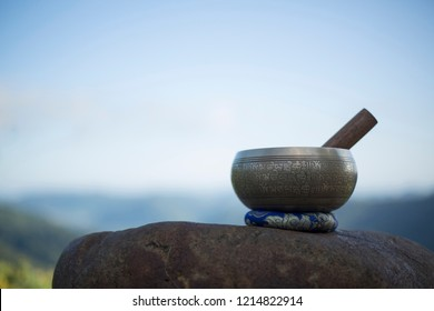 Tibetan singing bowl with sanskrit engraving pattern and sticks. on the rock.   natural background. copy space for text (The Nepali word on the tibetan singing bowls means wish everything is fine.)