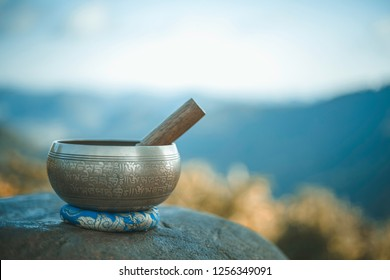 Tibetan singing bowl with sanskrit engraving pattern and sticks. on the rock. morning natural background. copy space (The Nepali word on the tibetan singing bowls means wish everything is fine