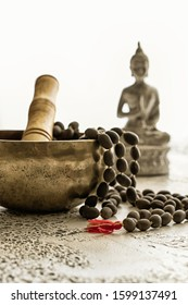 Tibetan singing bowl  with wooden mala beads and Buddha statue on white concrete background with copy space. Essential accessory for mindfulness or meditation