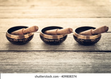 Tibetan singing bowls on wooden background
