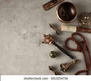 Tibetan singing copper bowl with a wooden clapper on a gray cement background, objects for meditation and alternative medicine, top view, copy space