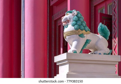Tibetan snow lion with turquoise mane in front of entrance to Buddhist temple. Symbol of snow Himalayan mountains & sky.
