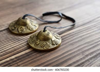 Tibetan Ting Sha Ceremonial Bells on wooden background closeup
