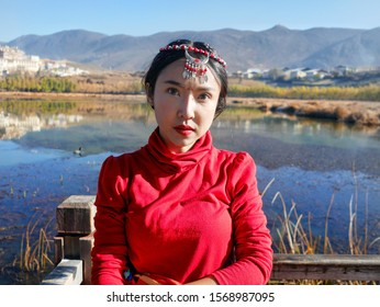 A Tibetan woman stands on a lake in the midst of Tibetan temples and mountains.