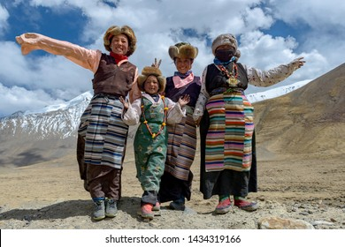 TIBET/CHINA - June 26, 2019: Smiling tibetan old women and her family in national colorful dress staying in the summer field in Tibet, China