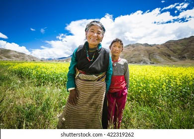 TIBET/CHINA - SEPTEMBER 11, 2014: Smiling tibetan old women and her 	 granddaughter in national colorful dress staying in the summer field in Tibet, China