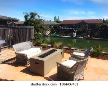 Tiburon, CA/USA - April 12, 2019: patio furniture pulled up to a gas firepit in a backyard along the lagoon