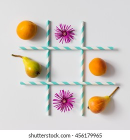 Tic tac toe made of  fruits, flowers and straws. Flat lay. Healthy food concept.